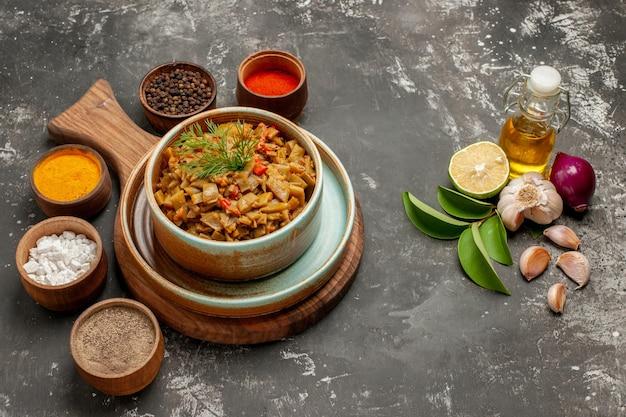 Vista ravvicinata laterale piatto e spezie cinque ciotole di spezie piatto di pomodori e fagiolini accanto alla bottiglia di foglie di olio e limone