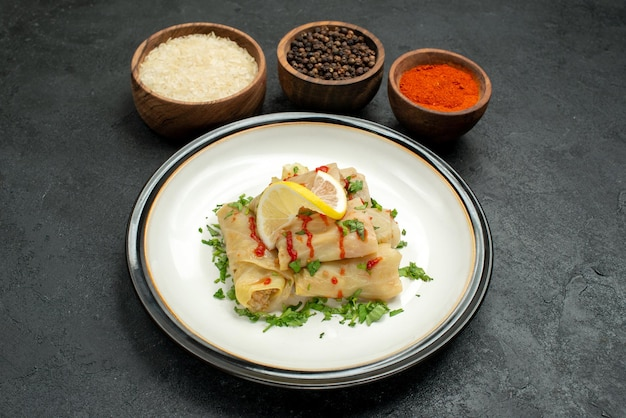 어두운 배경에 소스 레몬과 허브, 다채로운 향신료 쌀과 검은 후추 그릇과 함께 식욕을 돋우는 박제 양배추와 함께 측면 클로즈업 보기 요리