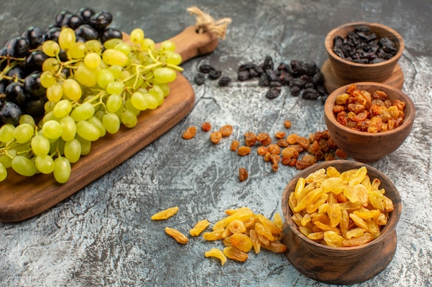 Side close-up view dried fruits bowls of the appetizing colorful dried fruits grapes on the board