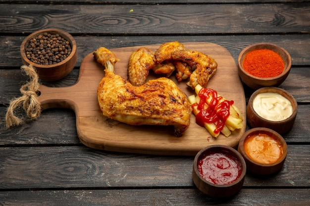 テーブルの上のケチャップ黒胡椒ソースとスパイスの横にあるキッチンボード上のファーストフードチキンとフライドポテトの側面のクローズアップビュー