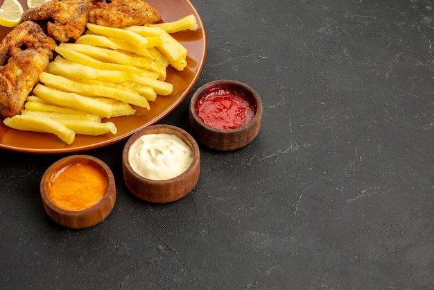Side close-up view fastfood orange plate of chicken wings appetizing french fries and lemon and three bowls of different types of sauces on the dark table