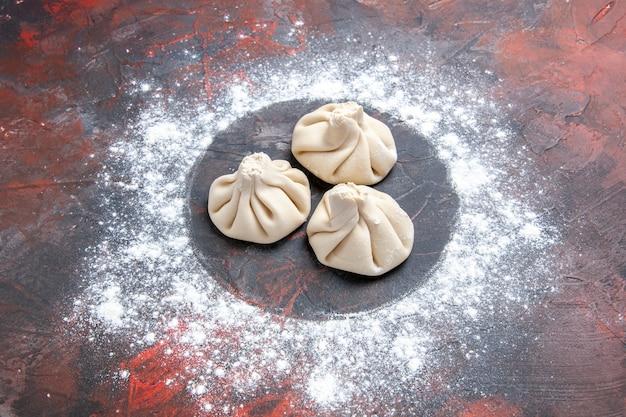 Vista ravvicinata laterale farina farina tre khinkali sul tavolo