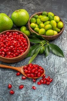 Vista ravvicinata laterale frutta mele agrumi nella ciotola semi di cucchiaio di melograno