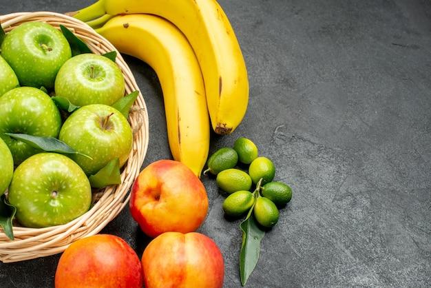 Vista ravvicinata laterale frutta banane mele nel cesto lime nettarine sul tavolo