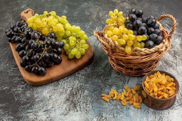 Vista ravvicinata laterale fruttifica il cesto e la tavola con l'uva accanto alla ciotola di frutta secca