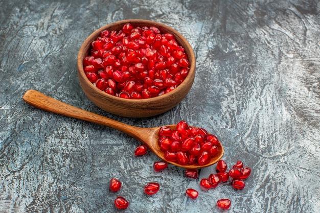 Vista ravvicinata laterale fruttiera ciotola di semi di melograno e cucchiaio sul tavolo