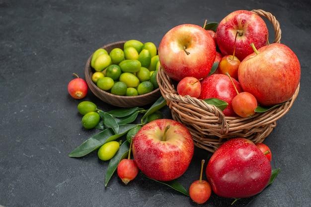 側面のクローズアップビューフルーツサクランボとリンゴの柑橘系の果物のバスケットの茶色のボウル