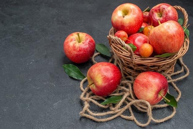バスケットロープの側面のクローズアップビューフルーツチェリーとリンゴ