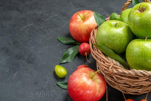 Vista ravvicinata laterale frutta ciliegie mele cesto di mele verdi con foglie