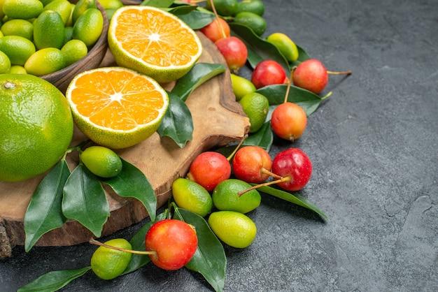 側面のクローズアップビューフルーツチェリー木の板に葉を持つ柑橘系の果物