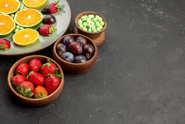 어두운 탁자의 왼쪽에 있는 다양한 과일과 과자 그릇 옆에 초콜릿으로 덮인 딸기 다진 오렌지와 녹색 사탕을 가까이에서 볼 수 있습니다.