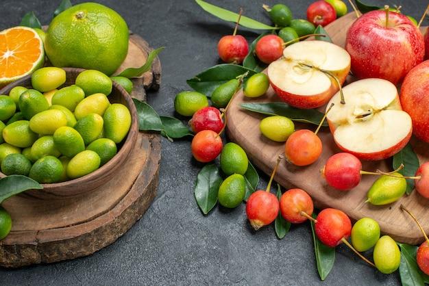 Vista ravvicinata laterale frutta agrumi in una ciotola mele rosse ciliegie sul tabellone