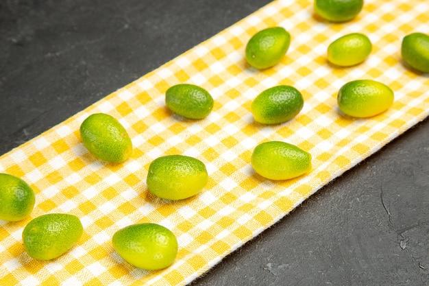 側面のクローズアップビューフルーツ柑橘系の果物、暗いテーブルの白黄色のテーブルクロス