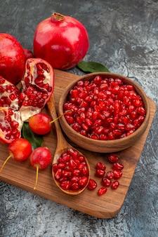 Vista ravvicinata laterale frutta il tagliere con semi di melograno cucchiaio ciliegie melograno