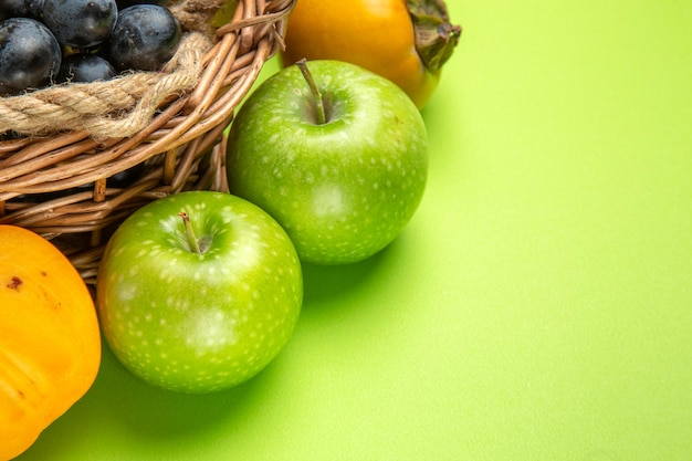 Side close-up view fruits green apples bunches of black grapes persimmons on the green table