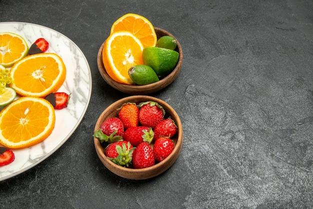 右側のテーブルのスライスされたオレンジレモンとチョコレートで覆われたイチゴのプレートの横にある柑橘系の果物とベリーのテーブルプレート上の側面のクローズアップビューフルーツ