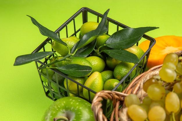 側面のクローズアップビューフルーツ柿リンゴ柑橘系の果物の緑のブドウのバスケットの束