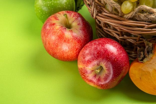 Вид сбоку крупным планом фрукты красные яблоки гроздья зеленого винограда хурма на зеленом столе