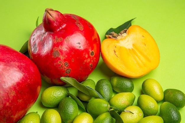 Вид сбоку крупным планом фрукты красные гранаты зелено-желтые цитрусовые хурма на столе