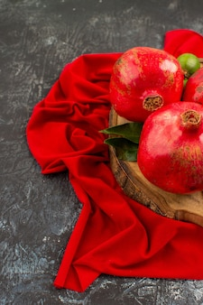 Side close-up view fruits ripe pomegranates on the wooden board on the red tablecloth
