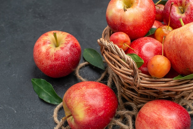 側面のクローズアップビューフルーツロープチェリーとかごの中のリンゴ