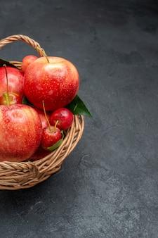 側面のクローズアップビューは、バスケットに葉を持つ食欲をそそるサクランボとリンゴを実らせます
