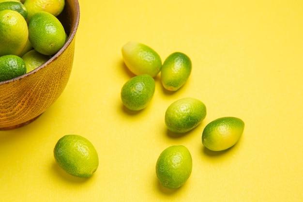 側面のクローズアップビューは、黄色いテーブルのボウルの横にある食欲をそそる果物を果物します