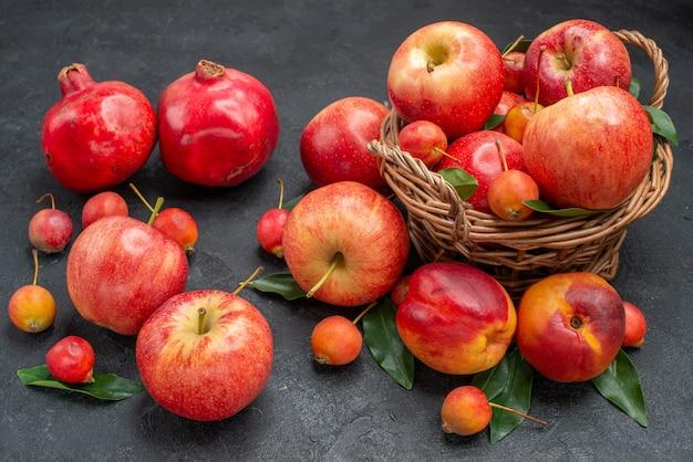 側面のクローズアップビューフルーツリンゴの木製バスケットチェリーはネクタリンザクロを残します