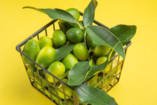 Vista ravvicinata laterale frutti con foglie frutti verdi con foglie nel cestino grigio