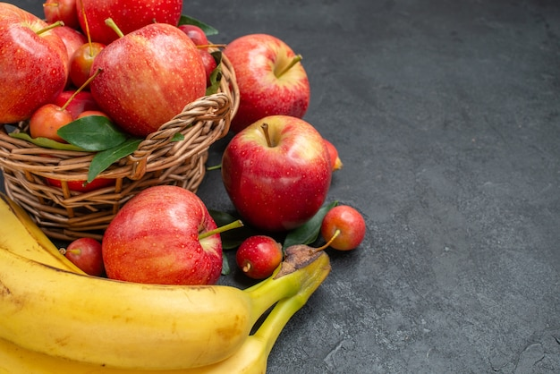 Side close-up view fruits wooden basket of apples and cherries bananas