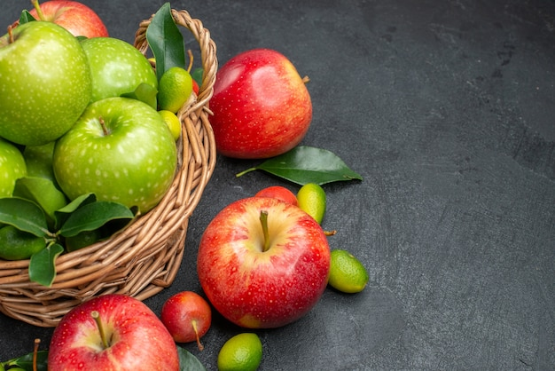 Side close-up view fruits wooden basket of green apples with leaves next to the berries and fruits