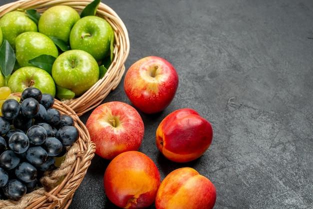 Vista ravvicinata laterale frutti cesti di legno di mele verdi e grappoli di uva nettarine