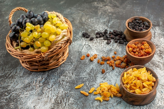 Side close-up view grapes bowls of dried fruits the appetizing grapes in the basket