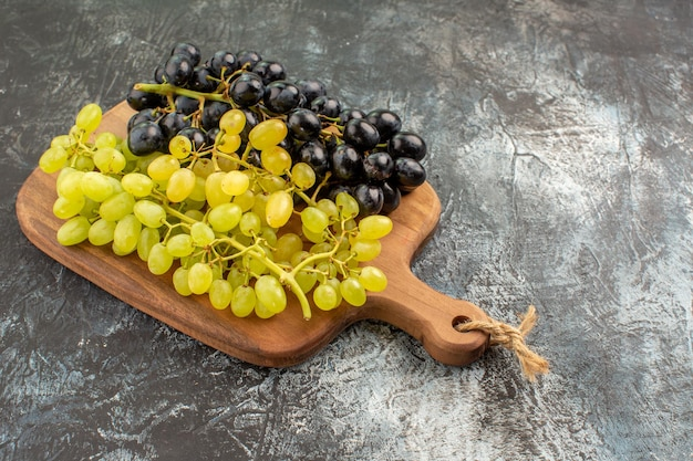 Side close-up view grapes wooden cutting board and bunches of the appetizing grapes