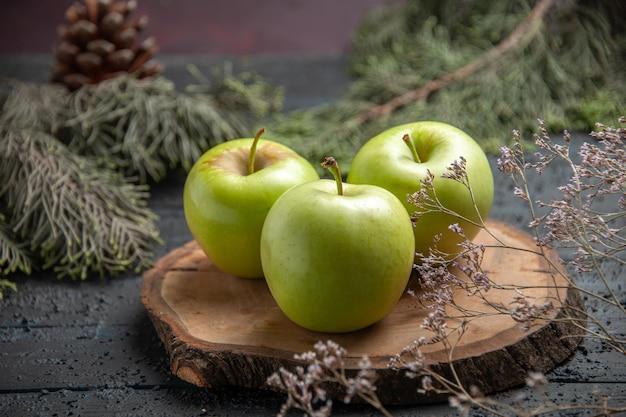 円錐形のトウヒの枝の横にある木の板に3つのリンゴを食欲をそそる側面のクローズアップビュー青リンゴ