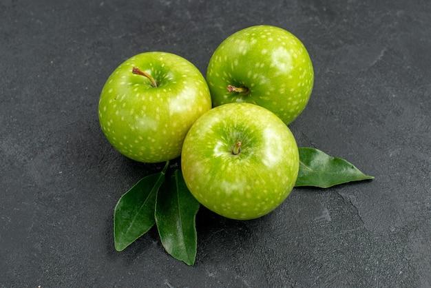 측면 클로즈업 보기 녹색 사과 어두운 탁자에 잎이 있는 식욕을 돋우는 녹색 사과