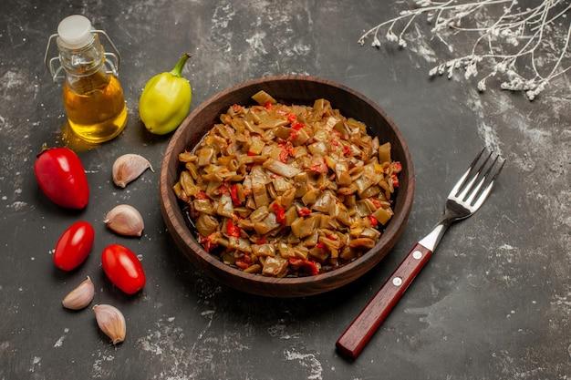 Vista ravvicinata laterale fagiolini piatto di fagiolini forchetta aglio pomodori peperoni e bottiglia di olio