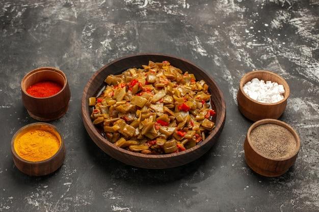 Vista ravvicinata laterale fagiolini e spezie fagiolini e pomodori tra quattro ciotole di spezie sul tavolo scuro