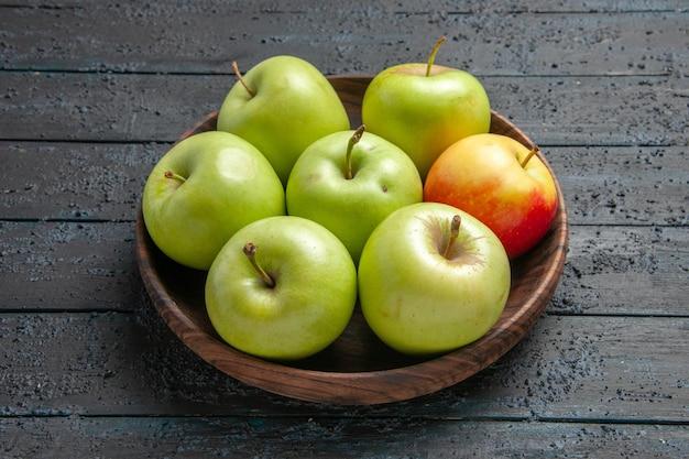 Vista ravvicinata laterale mele verde-giallo-rossastre una ciotola di mele rossastre gialle verdi sul tavolo grigio