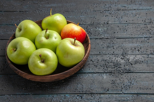 Vista ravvicinata laterale mele verdi-gialle-rossicce ciotola marrone di mele rossastre gialle verdi sul lato sinistro del tavolo grigio