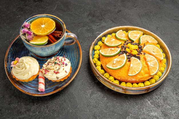 Side close-up view herbal tea blue cup of herbal tea with cinnamon sticks and lemon and two cupcakes with cream next to the plate of an appetizing cake with candies and limes on the black table