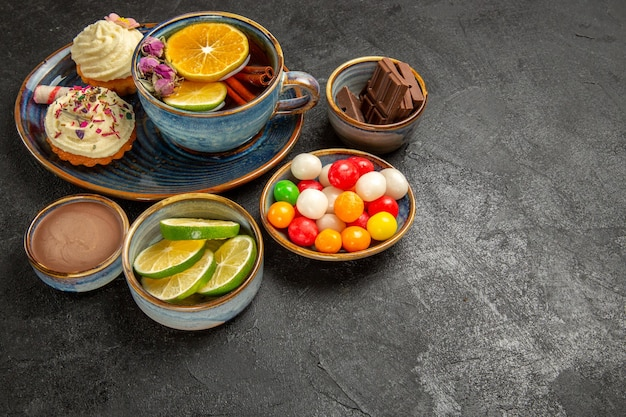 側面の拡大図レモンとお茶のカップの横にあるライムのカラフルなキャンディーのチョコレートクリームスライスのハーブティーボウルと黒いテーブルの上のクリームと2つのカップケーキ