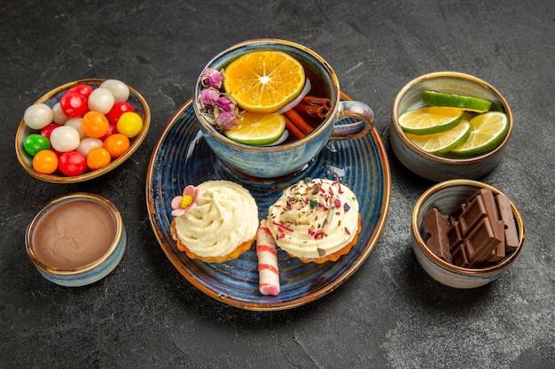 Боковой вид сбоку чаши для травяного чая с кусочками шоколада, шоколадным кремом с лаймом и красочными конфетами рядом с синей чашкой травяного чая и двумя кексами со сливками на черном столе