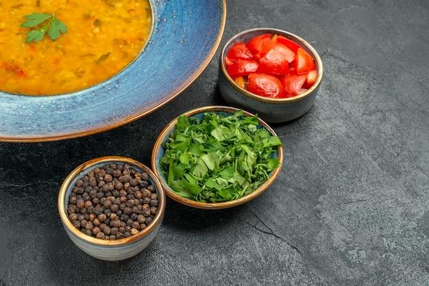 Вид сбоку крупным планом суп из чечевицы тарелка чечевичного супа три миски помидоров черный перец травы