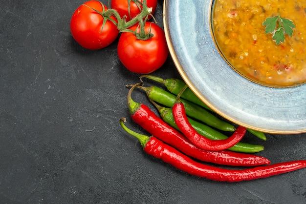 Vista ravvicinata laterale zuppa di lenticchie la zuppa di lenticchie appetitosa pomodori peperoncini rossi e verdi