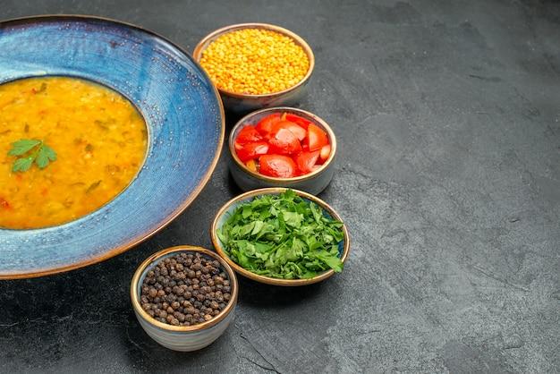Vista ravvicinata laterale zuppa di lenticchie zuppa di lenticchie accanto alle ciotole di spezie erbe pomodori