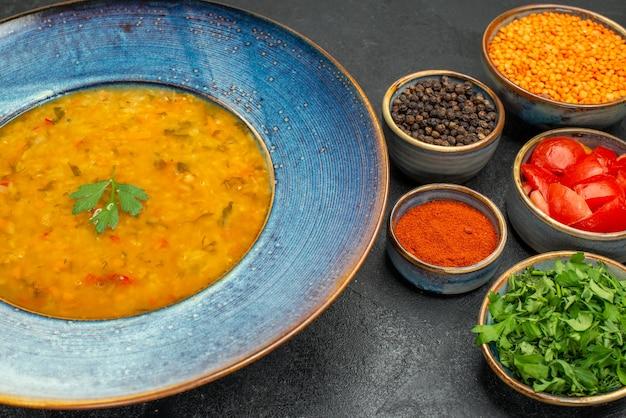 Vista ravvicinata laterale zuppa di lenticchie zuppa di lenticchie spezie pomodori lenticchie erbe nelle ciotole