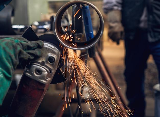 Вид сбоку крупным планом профессиональных трудолюбивых мужских рук режет металлическую трубу большой электрической шлифовальной машиной, в то время как искры летят в промышленной мастерской ткани или гараже.