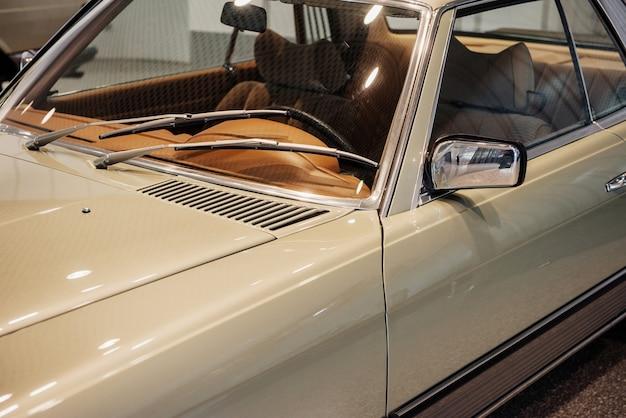 Вид сбоку крупным планом ретро-бежевого автомобиля с левым хромированным боковым зеркалом и отделкой окон, омывателями лобового стекла, коричневым салоном автомобиля.