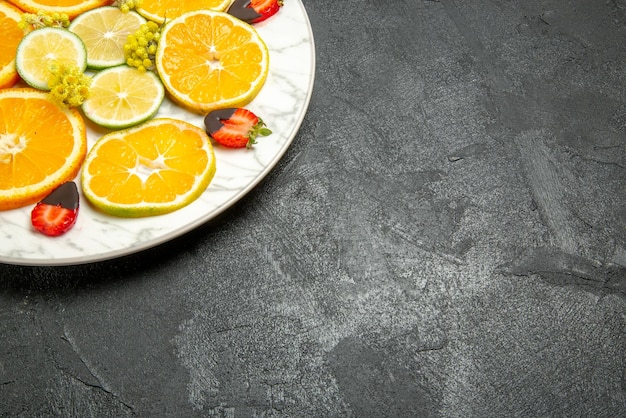 Vista ravvicinata laterale arancia e fragole piatto bianco di appetitose fragole e limoni ricoperti di cioccolato arancione sul lato sinistro del tavolo